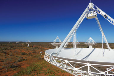 View through the side of a radio telescope dish towards other radio telescopes in the distance that form part of the ASKAP.