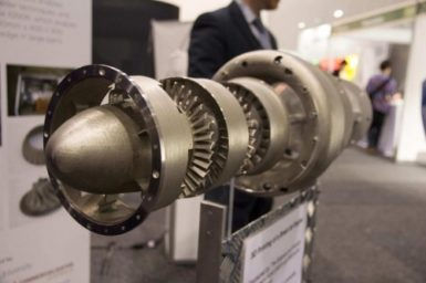 A 3D printed jet engine displayed on a stand.