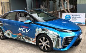 A bright blue Toyota Mirai which is a fuel cell vehicle that runs on hydrogen parked in front of a CSIRO banner