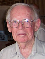 An elderly man with glasses looking at the camera