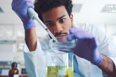 Scientist working with a pipette and laboratory equipment.