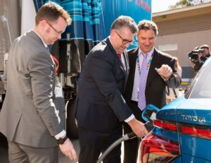 Three adult males in business suits standing next to a blue car. The male in the middle wearing glasses is holding a pipe with a nozzle in his right hand to fill the car with the purified hydrogen product. In the background is a camera operator filming the refuelling operation.