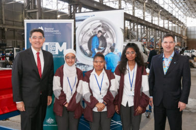 Three school girls standing between two men in suits in front of banners. they are standing in a very large shed with manufacturing and light industry activities taking place behind them.